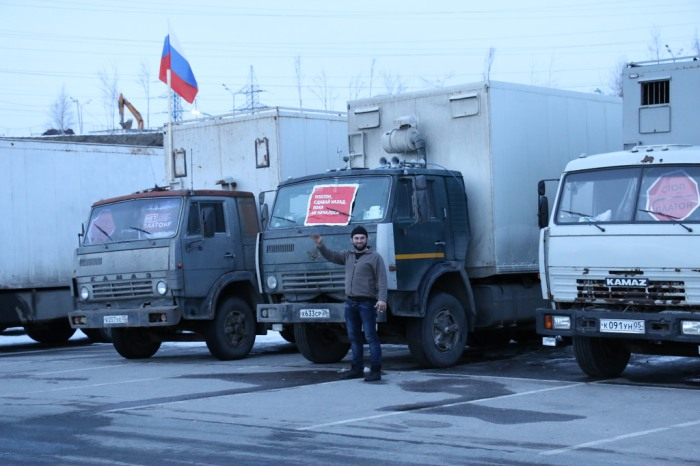 "Striking Dagestani trucker  in front of his rig. The placard on the windshield reads, ""Plato, put it into reverse before it kicks off."" Photo by and courtesy of anatrrra"