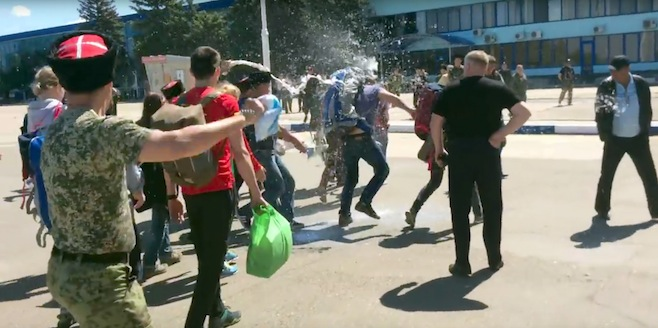 In this frame from video provided by Anapa Today, Cossacks throw milk at opposition leader Alexei Navally, center right, at the Anapa airport, southern Russia, Tuesday, May 17, 2016. A group of Cossacks attacked Russian opposition leader Alexei Navalny and his associates outside an airport in southern Russia Tuesday, injuring Navalny and six others, his spokeswoman said. (Dmitry Slaboda/Anapa Today via AP)