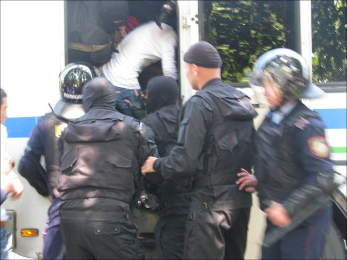 Riot police loading protesters onto a bus, Almaty, May 21, 2016