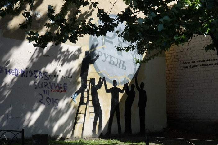 """Silhouette figures trying to keep a ten-ruble in the air next to an inscription that reads, """"Not everything is in our hands."""" Petersburg, May 23, 2016. Photo by the Russian Reader"""