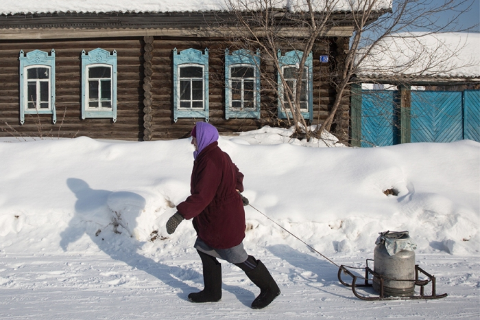 An elderly woman pulling a metal container with water past a snow-covered wooden house with carved window frames in the village of Kondratyevo, Omsk Region, February 17, 2017. Photo courtesy of Dmitry Feoktistov/TASS Россия. Омская область. 19 февраля 2017. Жительница села Кондратьево в Муромцевском районе Омской области. Дмитрий Феоктистов/ТАСС